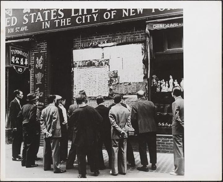 View of a crowd gathered around news bulletins in Chinese posted on a wall in Chinatown, 1944