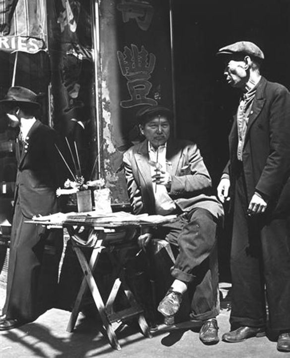 View of three Asian men in front of shop. The man in the center is seated behind a small folding table with newspapers and various items on top. - Circa 1940s